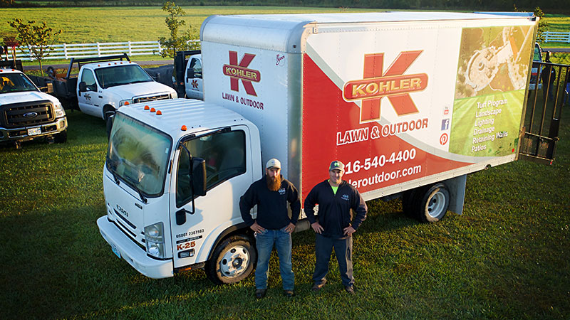 Turf Treatment. Image of Kohler Lawn & Outdoor truck with 2 employees.